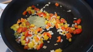 玉ねぎ、にんにく、ハーブを加えて炒めている